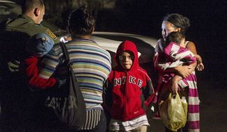 ** FILE ** In this photo taken July 3, 2014, mothers from Honduras traveling with their children prepare to get into a U.S. Customs and Border Protection Services agent's truck after crossing the Rio Grande near McAllen, Texas. (AP Photo/Austin American-Statesman, Rodolfo Gonzalez)