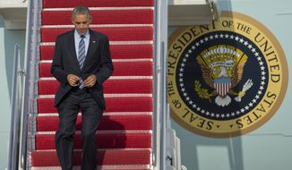President Barack Obama jogs down the ramp of Air Force One as he arrives Andrews Air Force Base, Md., Thursday, July 10,  2014.  (AP Photo/Manuel Balce Ceneta)