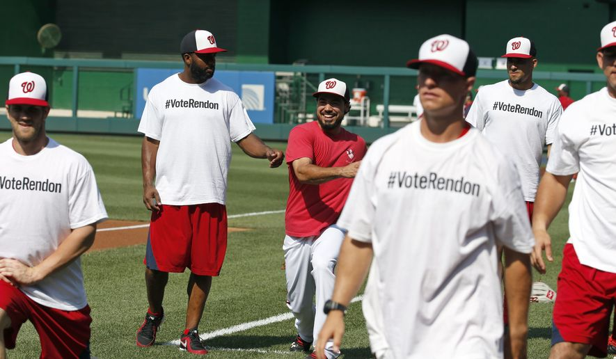 Washington Nationals' Anthony Rendon, third from left, smiles as he warms up with his teammates who were were wearing t-shirts in support of him for the All Star game before an interleague baseball game against the Baltimore Orioles at Nationals Park, Tuesday, July 8, 2014, in Washington. (AP Photo/Alex Brandon)
