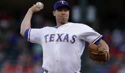 Texas Rangers starting pitcher Colby Lewis delivers to the Los Angeles Angels in the first inning of a baseball game, Thursday, July 10, 2014, in Arlington, Texas. (AP Photo/Tony Gutierrez)