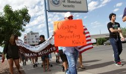 Marchers held signs as they made their way to Department of Homeland Security offices, protesting immigration policies Thursday, July 10, 2014, in El Paso, Texas. (AP Photo/El Paso Times, Victor Calzada)