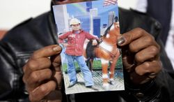 Francisco Ramos holds up a picture of his son, whose decomposed body was found in the Texas desert, as he waits for the arrival of his son's body, in Customs, in Guatemala City, Friday, July 11, 2014. The remains of Gilberto Francisco Ramos, the 15 year old boy who died in the Rio Grande Valley of South Texas, trying to reach the United States alone, was delivered to his family on Friday. (AP Photo/Moises Castillo)