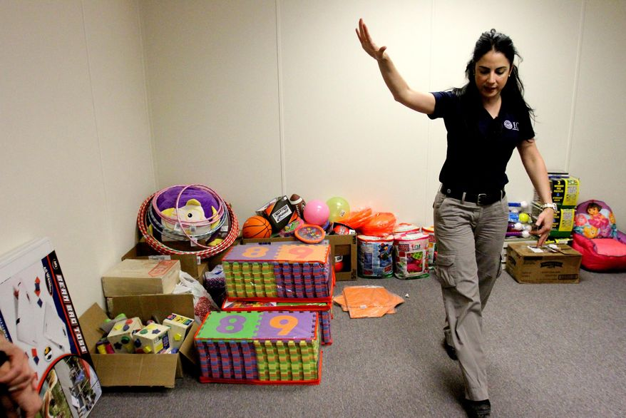 """Barbara Gonzalez, public information officer for Immigration and Customs Enforcement, shows a play room in an area where immigrant families are housed at the Artesia Residential Detention Facility inside the Federal Law Enforcement Center in Artesia, N.M. on Friday, July 11, 2014. U.S. Homeland Security Secretary Jeh Johnson visited the facility Friday and warned immigrants that """"we will send you back"""" if they try crossing into the country. (AP Photo/Pool, El Paso Times, Rudy Gutierrez)"""