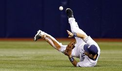 Tampa Bay Rays' Ben Zobrist cannot hold on to a line drive by Toronto Blue Jays' Jose Reyes, allowing two runs to score on the play during the fourth inning of a baseball game Friday, July 11, 2014, in St. Petersburg, Fla. (AP Photo/Mike Carlson)