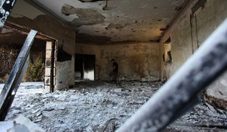 ** FILE ** This Sept. 13, 2012, file photo shows a man walking the burned shell of the U.S. Consulate, in Benghazi, Libya, after an attack that killed four Americans, including Ambassador J. Christopher Stevens. (AP photo/Mohammad Hannon, File)