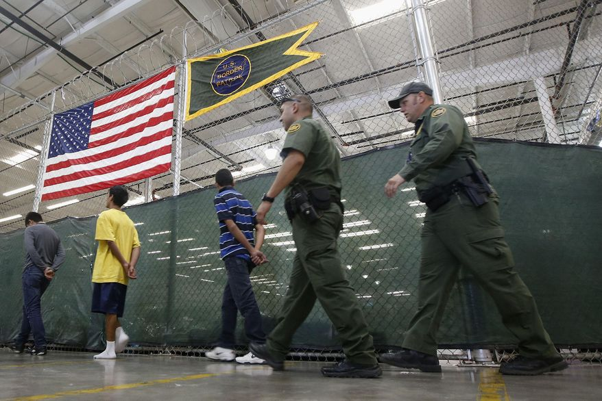 FILE - This June 18, 2014, file photo shows young detainees being escorted to an area to make phone calls as hundreds of mostly Central American immigrant children are being processed and held at the U.S. Customs and Border Protection Nogales Placement Center in Nogales, Ariz. (AP Photo/Ross D. Franklin, Pool, File)