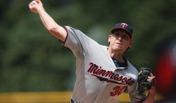 Minnesota Twins starting pitcher Kevin Correia works against the Colorado Rockies in the first inning of an interleague baseball game in Denver on Saturday, July 12, 2014. (AP Photo/David Zalubowski)
