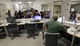 ** FILE ** This June 18, 2014, file photo, U.S. Customs and Border Protection agents work at a processing facility in Brownsville, Texas. (AP Photo/Eric Gay, Pool, File)
