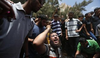 CAPTION CORRECTION, CORRECTS THE HOME WAS THAT OF POLICE CHIEF'S COUSIN - A Palestinian mourner chants slogans on the grave of a member of the al-Batsh family who were killed in Saturday's Israeli airstrike, during a funeral procession in Gaza City on Sunday, July 13, 2014. The strike hit the home of a cousin of Gaza police chief Taysir al-Batsh and damaged a nearby mosque as evening prayers ended Saturday, killing at least 18 people, wounding 50 and leaving some people believed to be trapped under the rubble, said Palestinian Health Ministry official Ashraf al-Kidra. (AP Photo/Lefteris Pitarakis)