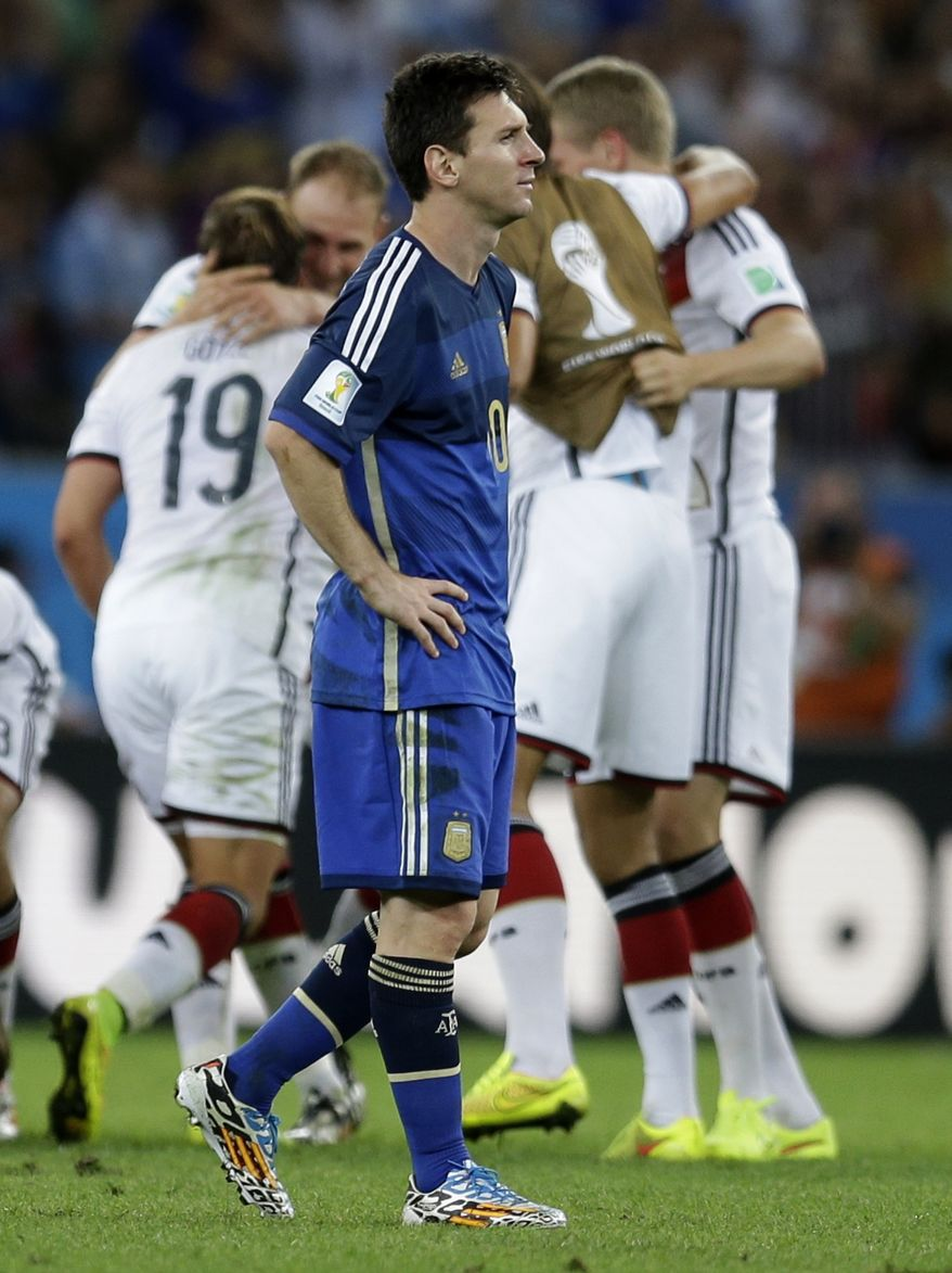 Argentina's Lionel Messi walks past as German players celebrate their 1-0 World Cup victory in extra time during the final soccer match between Germany and Argentina at the Maracana Stadium in Rio de Janeiro, Brazil, Sunday, July 13, 2014. (AP Photo/Natacha Pisarenko)