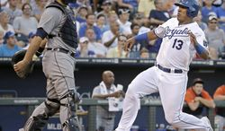 Kansas City Royals' Salvador Perez slides home past Detroit Tigers catcher Alex Avila to score on a sacrifice fly by Billy Butler during the sixth inning of a baseball game Saturday, July 12, 2014, in Kansas City, Mo. (AP Photo/Charlie Riedel)