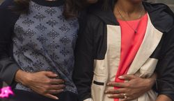 Malia Obama, left, and Sasha, right, with their mother, first lady Michelle Obama.  Malia was recently photographed in a Los Angeles restaurant before the photos were ordered taken down.  (AP Photo/Alexander F. Yuan)