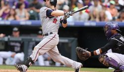 Minnesota Twins' Brian Dozier, left, follows the flight of his three-run home run as Colorado Rockies catcher Wilin Rosario looks on in the ninth inning of the Twins' 13-5 victory in an interleague baseball game in Denver on Sunday, July 13, 2014. Dozier hit a solo home run to lead off the eighth inning as well. (AP Photo/David Zalubowski)