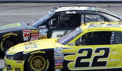 Brad Keselowski (22) slides down to pass Kyle Busch in turn two during the NASCAR Nationwide Series auto race at New Hampshire Motor Speedway Saturday, July 12, 2014, in Loudon, N.H. Keselowski went on to win the race, Busch came in second. (AP Photo/Jim Cole)