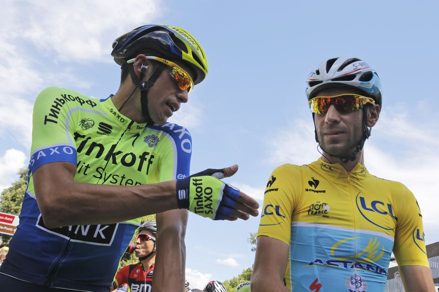 Spain's Alberto Contador gestures when talking to Italy's Vincenzo Nibali, wearing the overall leader's yellow jersey, prior to the start of the third stage of the Tour de France cycling race over 155 kilometers (96.3 miles) with start in Cambridge and finish in London, England, Monday, July 7, 2014. (AP Photo/Christophe Ena)