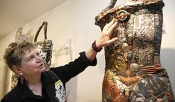In this July 10, 2014 photo, artist-activist Linda Stein runs her hand over the surface of one of her sculptural avatars, a wearable piece of art made of found objects designed to empower and protect the wearer, during a workshop and interactive gallery experience at her studio in New York.  Stein's artwork grew out of her sense of vulnerability in the wake of the Sept. 11 terror attacks. Her studio and living space are only blocks away from the attack site in lower Manhattan. (AP Photo/Kathy Willens)