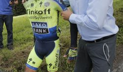 A doctor tends to Spain's Alberto Contador, as team manager Bjarne Riis of Denmark holds Contador after he crashed in the tenth stage of the Tour de France cycling race over 161.5 kilometers (100.4 miles) with start in Mulhouse and finish in La Planche des Belles Filles, France, Monday, July 14, 2014. Contador abandoned the race a bit later in the race. (AP Photo/Christophe Ena)