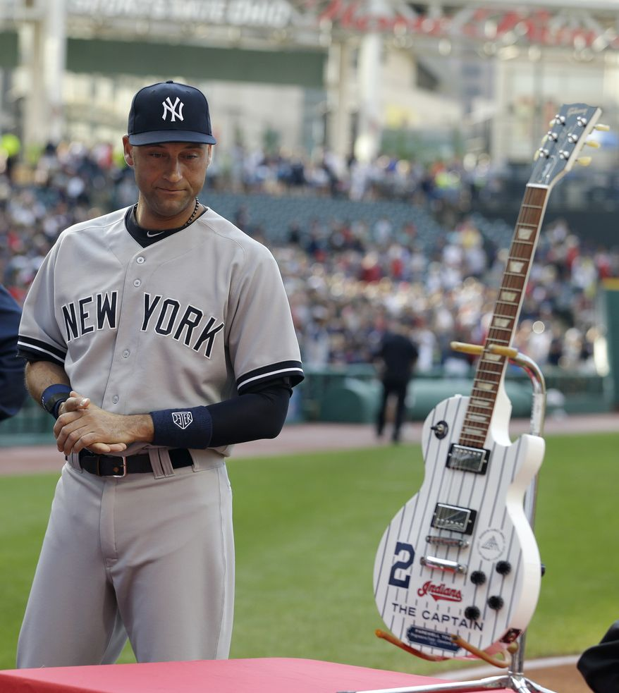 New York Yankees' Derek Jeter looks at a pin-striped guitar given to him by the Cleveland Indians organization before the Yankees play the Indians in a baseball game Thursday, July 10, 2014, in Cleveland. (AP Photo/Tony Dejak)