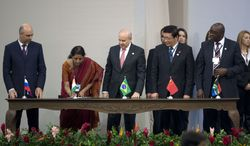 Russia's Finance Minister Anton Siluanov, left, India's Minister of State for Finance and Corporate Affairs Nirmala Sitharaman, second left, Brazil's Finance Minister Guido Mantega, center, China's Finance Minister Lou Jiwei, second right, and South Africa Finance Minister Nhlanhla Nene, right, sign an agreement creating a development bank during the BRICS 2014 summit in Fortaleza, Brazil, Tuesday, July 15, 2014. The leaders of the BRICS nations are meeting in Brazil for a summit where they are expected to officially create a bailout and development fund worth $100 billion. It's meant to be an alternative to the World Bank and the International Monetary Fund, which are seen as being dominated by the U.S. and Europe. (AP Photo/Silvia Izquierdo)
