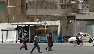 This image taken with a mobile phone camera shows people passing a black flag used by Islamic militants and a police cruiser belonging to the Islamic State group in front of the provincial government headquarters in Mosul, 225 miles (360 kilometers) northwest of Baghdad, Iraq, Tuesday, July 15, 2014. The panic that initially gripped Iraq after Sunni militants led by the Islamic State extremist group seized the country's second-largest city, Mosul, and swept across northern and western Iraq has largely subsided.(AP Photo)