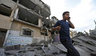 A Palestinian talks on a mobile phone as he walks on the rubble of a damaged house following an overnight Israeli missile strike in Gaza City, Tuesday, July 15, 2014. Egypt presented a cease-fire plan Monday to end a week of heavy fighting between Israel and Hamas militants in the Gaza Strip that has left at least 185 people dead, and both sides said they were seriously considering the proposal. The late-night offer by Egypt marked the first sign of a breakthrough in international efforts to end the conflict. (AP Photo/Lefteris Pitarakis)