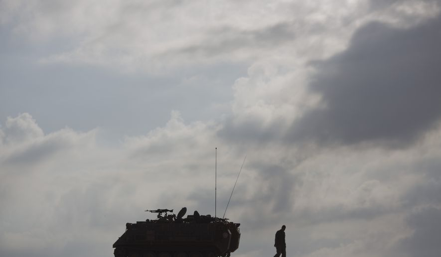 An Israeli soldiers walks by a military vehicle near the Israel Gaza Border, early Tuesday, July 15, 2014. The Israeli Cabinet has accepted an Egyptian proposal for a cease-fire to end a week of conflict with Hamas militants in the Gaza Strip that has killed 185 Palestinians and exposed millions of Israelis to Hamas rocket fire. No Israelis have been killed as a result of Hamas rocket launches. A senior Hamas official says the Palestinian militant group rejects an Egyptian proposal for a cease-fire with Israel. (AP Photo/Ariel Schalit)