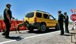 U.S. Border Patrol Senior Agent B.T. Hick and his dog Mirza, left, inspect a car at a check point outside Organ Pipe Cactus National Park in Why, Ariz., Wednesday, May 24, 2006. The detention of a prominent immigration activist at a Texas airport served as a reminder of the latitude the Border Patrol has in conducting checkpoints for drugs and immigrants in the country illegally at locations not on the border. (AP Photo/Matt York, File)