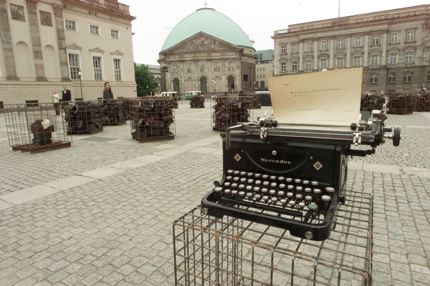 """**FILE** The """"Writer's Block"""" in Berlin's Bebel Square marks on May, 10, 1999, the 60th anniversary of a mass-burning of books 66 years ago. Cages filled with typewriters from the twenties and thirties sit on the squares, where Nazis burnt books of foreign and German writers on May 10, 1933. The display by Sheryl Oring from Grand Forks, North Dakota is accompanied by a dance performance. (Associated Press)"""