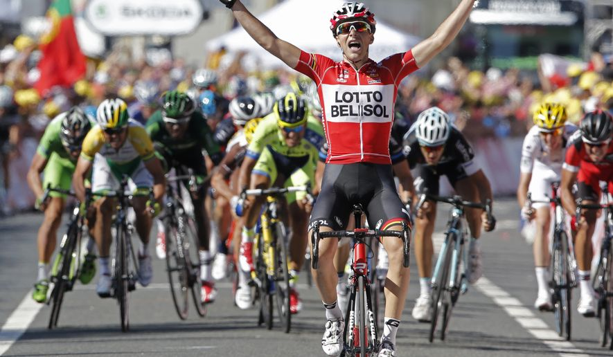 France's Tony Gallopin manages to stay ahead of the spring pack, rear, as he crosses the finish line to win the eleventh stage of the Tour de France cycling race over 187.5 kilometers (116.5 miles) with start in Besancon and finish in Oyonnax, France, Wednesday, July 16, 2014. (AP Photo/Peter Dejong)
