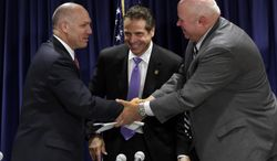 Anthony Simon, general chairman of the United Transportation Union, left, and Metropolitan Transportation Authority Chairman Thomas Prendergast, right, shake hands in front of Gov. Andrew Cuomo after a tentative labor agreement was reached at Cuomo's office in New York on Thursday, July 17, 2014. (AP Photo/Richard Drew)