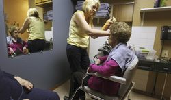 In this June 27, 2014 photo, cosmetologist Cindi Root finishes up styling resident Edith Lee's hair at Golden Good Shepherd Home in Golden, Ill. The nursing and rehabilitation home is getting a four-room addition, plus a beauty shop and a spa. The 42-bed home generally stays full and has a waiting list, making it difficult to serve people who counted on making Good Shepherd their home.  (AP Photo/The Quincy Herald-Whig, Steve Bohnstedt)