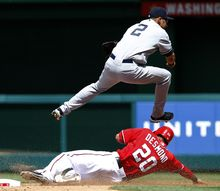 New York Yankees shortstop Derek Jeter (2) jumps over Washington Nationals' Ian Desmond (20) to complete the double play during the fourth inning of a baseball game at Nationals Park on Sunday, June 17, 2012, in Washington. Nationals' Danny Espinosa was out at first. The Yankees won 4-1. (AP Photo/Alex Brandon)