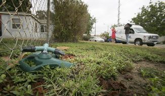 A lawn sprinkler is seen at the Whitney's home lawn, as television crews report on California's drought in Glendora, Calif., Thursday, July 17, 2014. The Southern California couple who scaled back watering due to drought received a letter from the city of Glendora warning that they could face fines if they don't get their brown lawn green again. They are told if they don't revive the lawn they could be hit with up to $500 in fines and possible criminal action. City Manager Chris Jeffers says the couple has not been cited and called it a friendly letter prompted by a neighbor's complaint. (AP Photo/Damian Dovarganes)