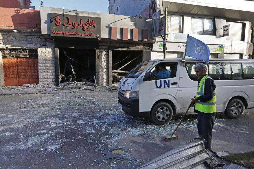 A Palestinian municipality worker sweeps the streets from glass, as a United Nations vehicle drives past a damaged money exchange post, following an overnight Israeli missile strike in Gaza City, Thursday, July 17, 2014. The Israeli military says it has struck 37 targets in Gaza ahead of a five-hour humanitarian cease-fire meant to allow civilians to stock up after 10 days of fighting. The Gaza Interior Ministry says four people were killed and that a 75-year-old woman died of wounds from the day before. The Israeli army says Hamas fired 11 rockets at Israel early Thursday. Palestinian health officials say that in total, at least 225 Palestinians have been killed. On the Israeli side, one man was killed since July 8.(AP Photo/Lefteris Pitarakis)