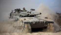 An Israeli tank moves into position near Israel and Gaza border, Friday, July, 18, 2014. Israeli troops pushed deeper into Gaza on Friday to destroy rocket launching sites and tunnels, firing volleys of tank shells and clashing with Palestinian fighters in a high-stakes ground offensive meant to weaken the enclave's Hamas rulers. Israel launched the operation late Thursday, following a 10-day campaign of more than 2,000 air strikes against Gaza that had failed to halt relentless Hamas rocket fire on Israeli cities. .(AP Photo/Dusan Vranic)