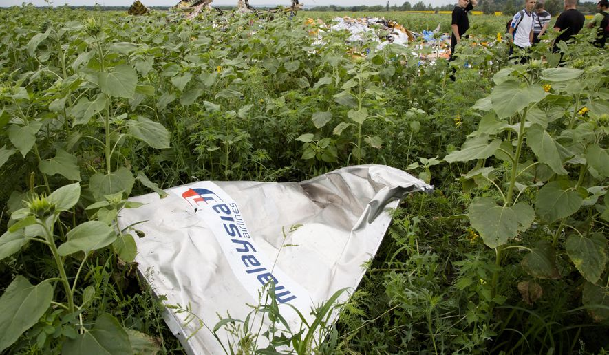 "A piece of a plane with the sign ""Malaysia Airlines"" lies in the grass as a group of Ukrainian coal miners search the site of a crashed Malaysian passenger plane near the village of Rozsypne, Ukraine, eastern Ukraine Friday, July 18, 2014. Rescue workers, policemen and even off-duty coal miners were combing a sprawling area in eastern Ukraine near the Russian border where the Malaysian plane ended up in burning pieces Thursday, killing all 298 aboard. (AP Photo/Dmitry Lovetsky)"