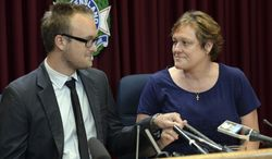 ** FILE ** In this March 25, 2014, photo, Kaylene Mann, right, and Jayden Burrows hold hands as they read a statement to the media in Brisbane, Australia, about the loss of Rod Burrows, who is Kaylene's brother and Jayden's father. Rod Burrows was among six Australians killed when Malaysia Airlines flight MH370 crashed into the Southern Indian ocean.  On Friday, July 18, 2014, Mann found out that her stepdaughter, Maree Rizk, was killed along with 297 others on Malaysia Airlines Flight 17, which U.S. intelligence authorities believe was shot down by a surface-to-air missile. (AP Photo/AAP, Dan Peled)