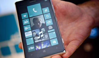 FILE - This Aug. 15, 2013 file photo shows Nokia's Lumia 925 phone at the flagship store of Finnish mobile phone manufacturer Nokia in Helsinki, Finland. On Thursday, July 17, 2014, as part of an announcement to cut up to 18,000 jobs over the next year, Microsoft said it would discontinue its Nokia X phones and shift future product designs to its Lumia line of Windows phones. (AP Photo/Lehtikuva, Mikko Stig, File) FINLAND OUT