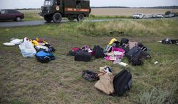 Passengers' personal luggage is collected at the site of a crashed Malaysia Airlines passenger plane near the village of Rozsypne, Ukraine, eastern Ukraine Friday, July 18, 2014. Rescue workers, policemen and even off-duty coal miners were combing a sprawling area in eastern Ukraine near the Russian border where the Malaysian plane ended up in burning pieces Thursday, killing all 298 aboard. (AP Photo/Dmitry Lovetsky)