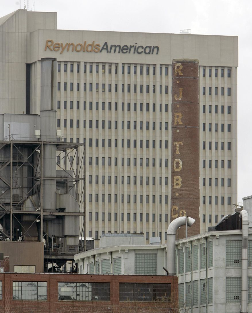In this Feb. 6, 2008 photo, a smokestack of an old R.J. Reynolds Tobacco plant frames the Reynolds American building in Winston-Salem, N.C., A Florida jury has slammed R.J. Reynolds Tobacco Co. with $23.6 billion in punitive damages in a lawsuit filed by Cynthia Robinson, the widow of a longtime smoker who died of lung cancer in 1996.  The damages the jury awarded to Robinson on Friday, July 18, 2014, after a four-week trial come in addition to $16.8 million in compensatory damages.  (AP Photo/Chuck Burton)