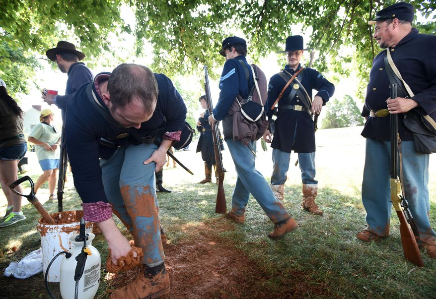 """ADVANCED FOR RELEASE SUNDAY, JULY 20, 2014 Aaron Sterling, of Lynchburg, adds more mud to his pants during filming in Appomattox, Va on Tuesday on July 15, 2014 at the Appomattox Court House National Historical Park.  On the day of Robert E. Lee's surrender to U.S. Grant in 1965, Union troops had marched 35 miles in the rain.  """"They would have been covered with mud,"""" Sterling said. (AP Photo/The News & Advance, Jill Nance)"""
