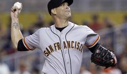 San Francisco Giants' Tim Hudson delivers a pitch during the first inning of a baseball game against the Miami Marlins, Saturday, July 19, 2014, in Miami. (AP Photo/Wilfredo Lee)
