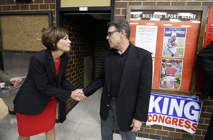 Texas Gov. Rick Perry greets Iowa Lt. Gov. Kim Reynolds, left, during a meeting with local party activists, Saturday, July 19, 2014, in Algona, Iowa. After his presidential bid crashed in 2012, Iowans now have to decide whether to give Perry another spin. (AP Photo/Charlie Neibergall)