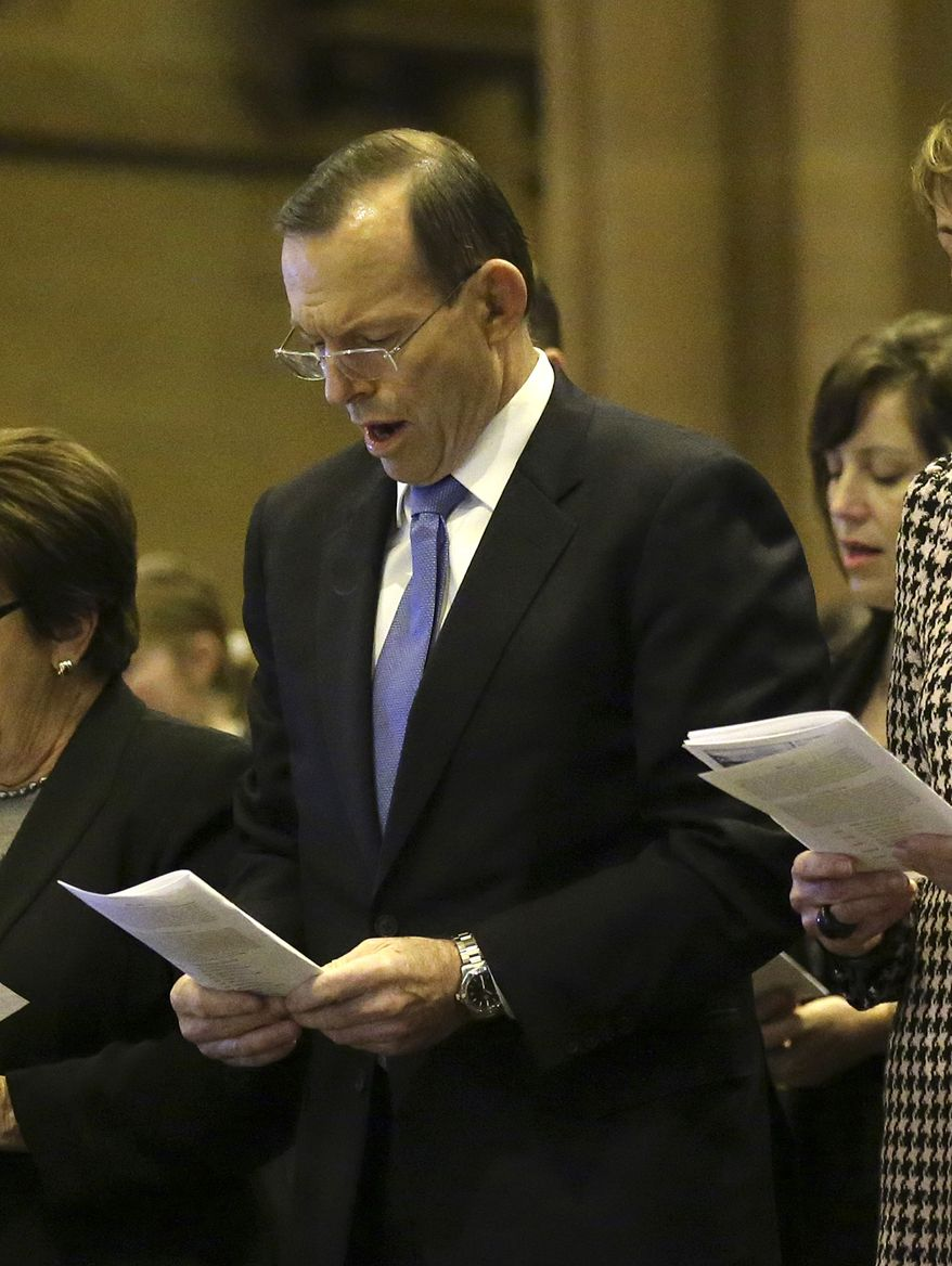 ** FILE ** Australia's Prime Minister Tony Abbott sings a hymn during a Mass at St. Mary's Cathedral commemorating victims of Malaysia Airlines Flight 17 in Sydney, Australia, Sunday, July 20, 2014.(AP Photo/Rob Griffith)