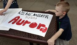 "** FILE ** In this  July 19, 2013, file photo, 4-year-old Jake Richards watches as his sister Stephanie makes signs reading ""Remember Aurora,"" during a remembrance event at which the names of people killed by gun violence in America over the previous year were read aloud, at Cherry Creek State Park in Aurora, Colo. (AP Photo/Brennan Linsley, file)"