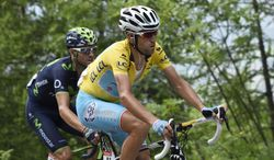 Spain's Alejandro Valverde, left, follows Italy's Vincenzo Nibali, wearing the overall leader's yellow jersey, during the fourteenth stage of the Tour de France cycling race over 177 kilometers (110 miles) with start in Grenoble and finish in Risoul, France, Saturday, July 19, 2014. (AP Photo/Eric Feferberg, Pool)