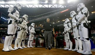 """** FILE ** The umpire crew, lead by Doug Eddings, walks onto the field as they are flanked by people dressed as stormtroopers from the """"Star Wars"""" films on Star Wars Day at Chase Field prior to a baseball game between the Arizona Diamondbacks and the Chicago Cubs on Sunday, July 20, 2014, in Phoenix. (AP Photo/Ross D. Franklin)"""