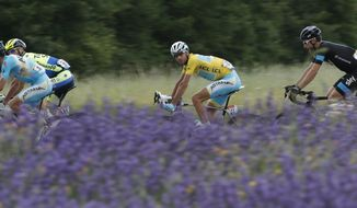 Italy's Vincenzo Nibali, wearing the overall leader's yellow jersey, looks at the photographer as he rides in the pack with Italy's Michele Scarponi, left, Ireland's Nicolas Roche, second left, and Austria's Bernhard Eisel, right, when passing a lavender field during the fifteenth stage of the Tour de France cycling race over 222 kilometers (137.9 miles) with start in Tallard and finish in Nimes, France, Sunday, July 20, 2014. (AP Photo/Christophe Ena)