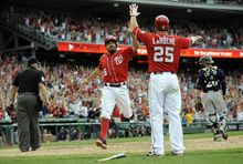 Washington Nationals' Anthony Rendon (6) celebrates after he scored the winning run with Adam LaRoche (25) on a walk off hit by Jayson Werth with during the ninth inning of a baseball game as Milwaukee Brewers catcher Jonathan Lucroy looks on at right, Sunday, July 20, 2014, in Washington. The Nationals won 5-4.  (AP Photo/Nick Wass)