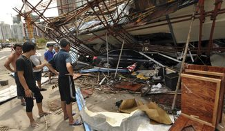 In this Saturday, July 19, 2014 photo released by China's Xinhua News Agency, a vehicle sits under a collapsed building after landfall of typhoon Rammasun in Haikou, capital of south China's Hainan Province. The strongest typhoon to hit southern China in four decades has killed more than a dozen people, the government said Sunday. (AP Photo/Xinhua, Xia Yifang) NO SALES